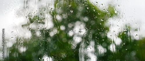 Obraz View through the window to garden of house, raining. Rainfall outside the window or outside the glass, Rain drops on window or on glass. - fototapety do salonu