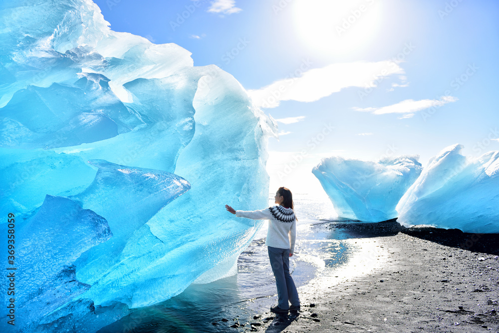 Fototapeta Iceland Amazing landscape at Iceberg beach. Tourist by icebergs on Ice beach, Breidamerkursandur aka Diamond Beach by jokulsarlon glacial lagoon / glacier lake nature. Woman in icelandic sweater.