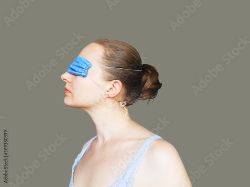 Fotografía Young woman with face mask on eyes, conspiracy theorists are a real thing and co