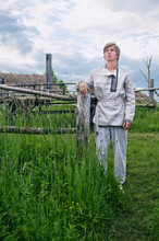 Village Young Man Stands Near An Old Wooden Fence In A Field