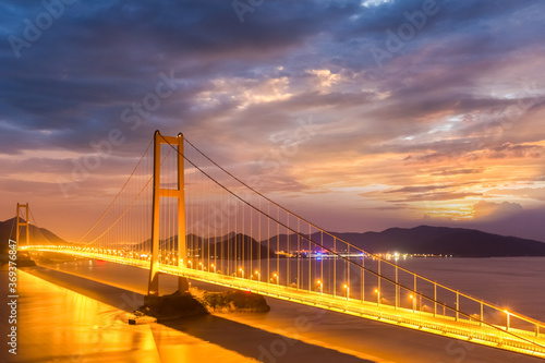 Fototapeta bridge spanning the sea in nightfall