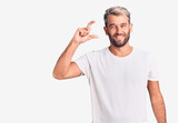 Young handsome blond man wearing casual t-shirt approving doing positive gesture with hand, thumbs up smiling and happy for success. winner gesture.