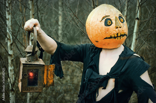 Slika na platnu Halloween Scarecrow with a pumpkin on his head and an antique lantern in his han