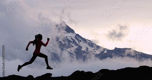 Obraz Running woman athlete sport concept. Trail runner exercising in mountain summit background. Female runner on run training outdoors living active fit lifestyle. Silhouette at sunset. - fototapety do salonu