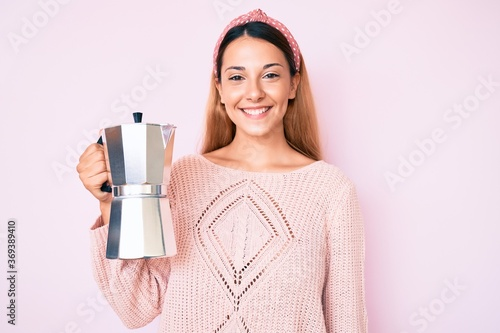 Fotografie, Obraz Young brunette woman holding italian coffee maker looking positive and happy sta