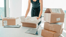 Selling Clothing From Home. Small Business Entrepreneur Woman Packing Dress Clothes In Mailing Box For Shipping From Online Store.