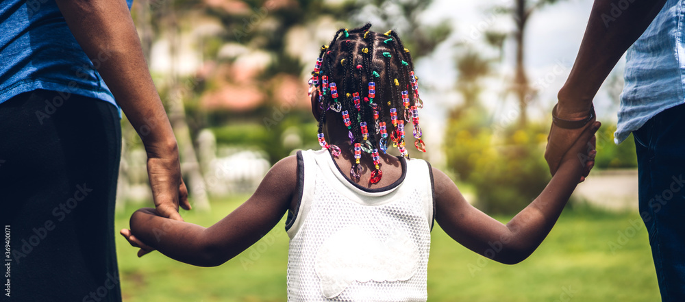 Fototapeta Portrait of enjoy happy love black family african american father and mother holding little african girl hand in moments good time in summer park at home