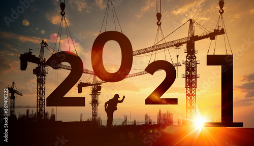 Fotografía Cranes building construction 2021 year sign,Silhouette staff works as a team to