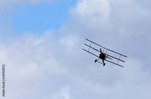 Canvas Vintage  Sopwith Triplane in flight with clouds and blue sky.