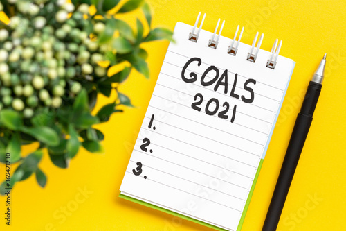 Fototapeta The inscription Goals 2021 on a white notepad and green plant on yellow background