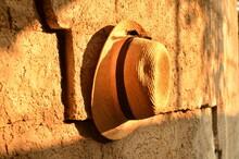Cappello Di Paglia Appeso Ad Un Muro Con La Luce Arancione Del Sole Che Tramonta.