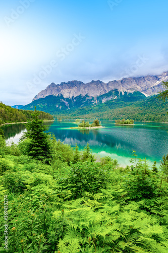 Obraz Small islands with pine-trees in the middle of Eibsee lake with Zugspitze mountain. Beautiful landscape scenery with paradise beach and clear blue water in German Alps, Bavaria, Germany, Europe. - fototapety do salonu