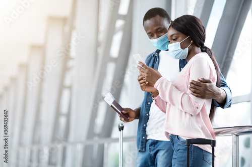 Obraz Black Couple Of Travellers Wearing Medical Masks In Airport, Waiting For Flight - fototapety do salonu