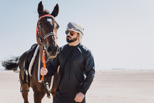 Man With Horse Standing In Des...