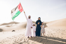 Happy Family With United Arab Emirates Flag Standing On Sand Dune