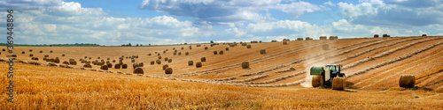 Foto large panorama of a field with bales of straw, a tractor with a baler harvesting