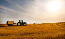 Tractor With Baler For Harvesting Straw, Harvesting Hay On The Hills In The Evening