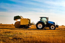 Tractor With Bale Machine For Harvesting Straw In The Field And Making Large Round Bales. Agricultural Work, Harvesting Hay On The Hills In A Summer Field