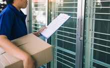 Midsection Of Delivery Man Holding Paper And Package While Standing At Entrance