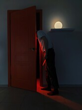 Man With Knife Looking Through Door In Illuminated Room At Home