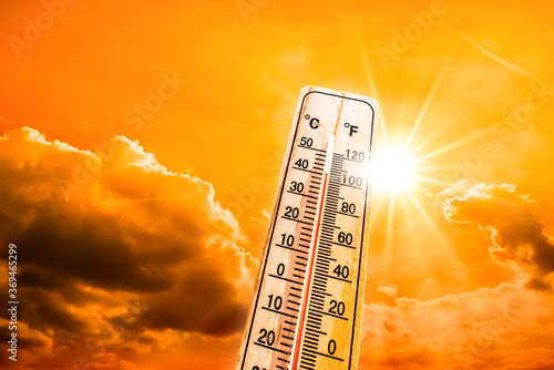 Hot summer or heat wave background, glowing sun on orange sky with thermometer Fotobehang