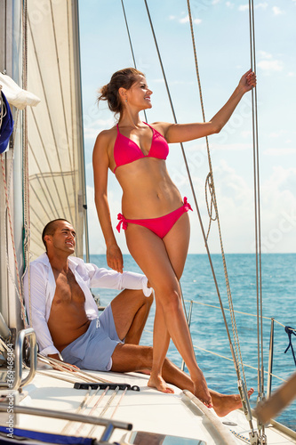Young attractive pleasant woman enjoying sea trip with boyfriend on deck of their sailboat on sunny summer day