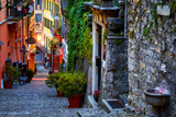 Fototapeta Na drzwi - Bellagio, lake Como, Milan, Italy. Famous stone stairs street. Evening Nighttime with blue sky and lights of outdoor lanterns. Picturesque italian architecture of famous luxury Alpine health resort