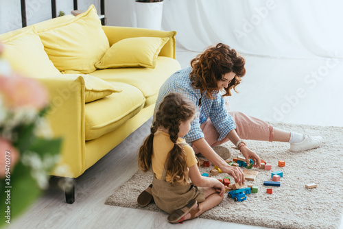 Obraz selective focus of young nanny and kid sitting on floor and playing with multicolored blocks - fototapety do salonu