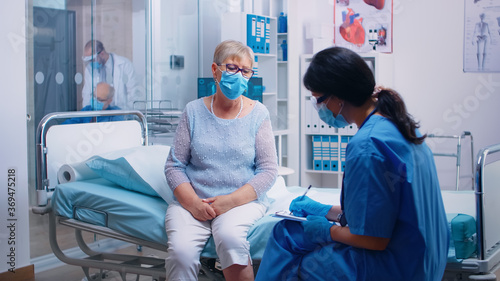 Foto Nurse in protective equipment questioning senior lady patient who wears a mask