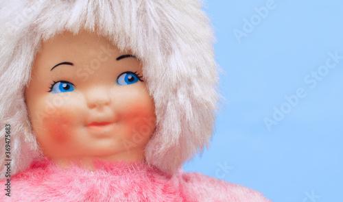 Obraz na plátně Child's doll on blue close up with copy space