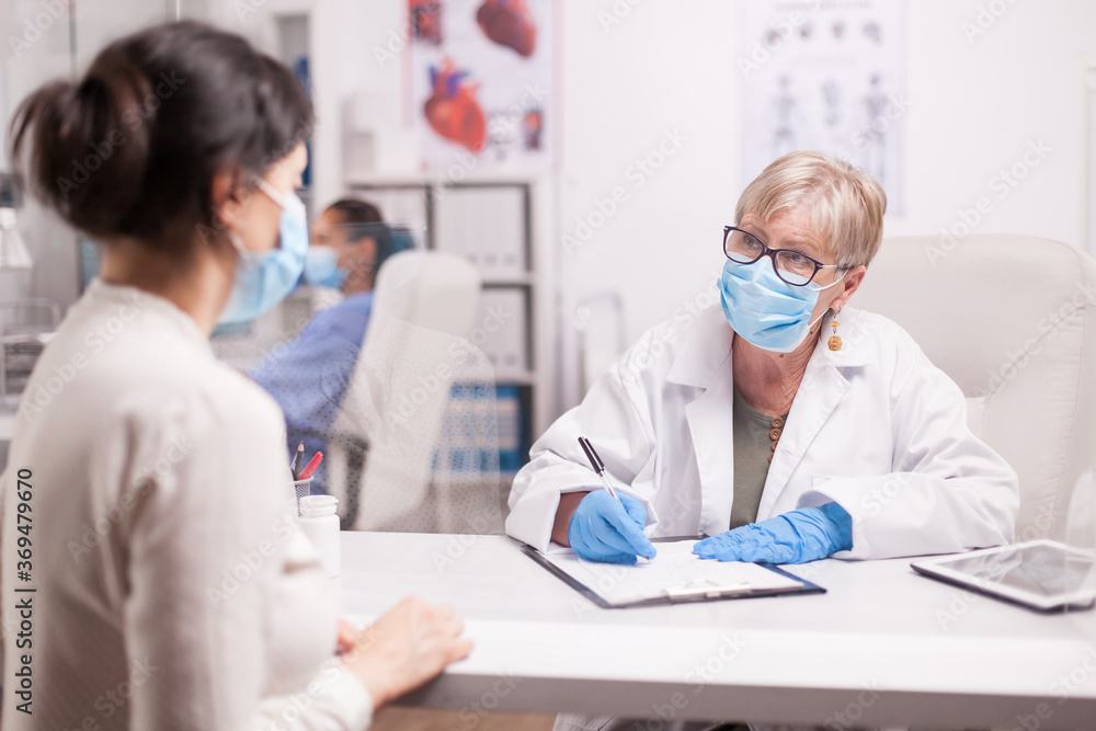 Fototapeta Doctor wearing protection mask against covid taking notes during consultation with patient in medical clinic. Nurse wearing blue uniform while working on computer.