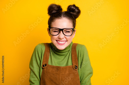 Closeup photo of attractive lady two funny pretty buns good mood high school student giggling overjoyed wear specs green pullover brown overall isolated bright yellow color background