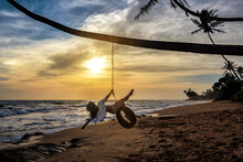 Girl Swing On Tire At The Beach