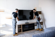 Full Length Shot Of Two Professional Technicians, Workers In Uniform Installing Television On The Wall Indoors. Construction, Maintenance And Delivery Concept