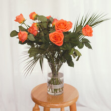 Closeup Shot Of  Vintage Style Orange Flowers In Glass Vase Isolated On A Wooden Surface