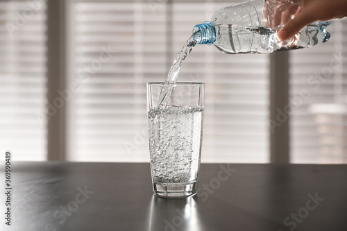 Person pouring water from bottle into glass on table against blurred background, Wallpaper Mural
