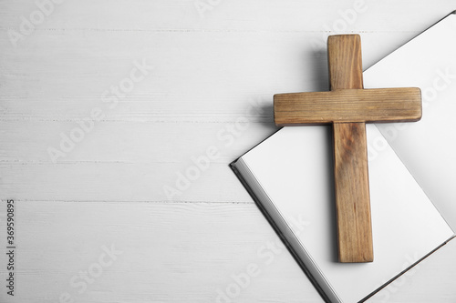 Photo Christian cross and Bible on white wooden background, flat lay with space for text