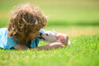 canvas print picture - Cute boy child with her doggy lying on lawn. Kid with pet puppy dog. Emotions of people.