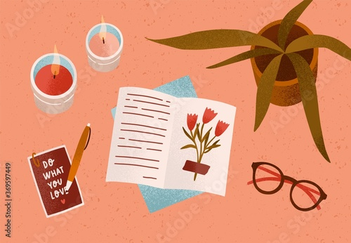 Obraz Notepad or diary with dry beautiful flower and writing text surrounded by cosiness things on desk vector flat illustration. Top view of cozy workplace organization with candles, accessories and plant - fototapety do salonu