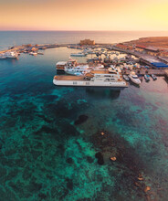 Beautiful Aerial Sunset Shot Of Paphos Castle And Paphos Harbor In Cyprus. Crystal Clear Water, Fishing Boats, Luxury Yachts - Amazing Travel Destination For All Year Vacation.
