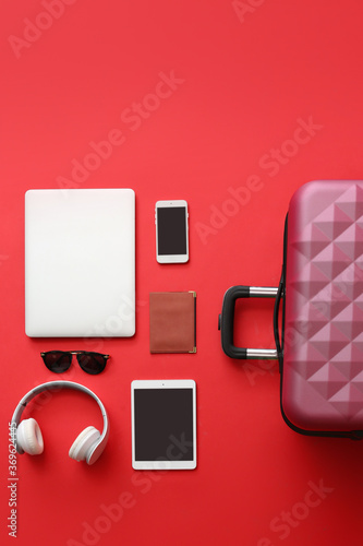 Obraz Packed suitcase with accessories and devices on color background. Travel concept - fototapety do salonu