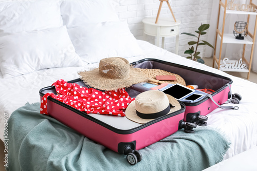 Obraz Packed suitcase with beach accessories on bed. Travel concept - fototapety do salonu