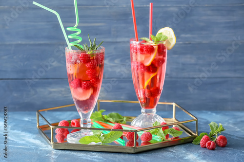 Glasses of cold raspberry tea on color background