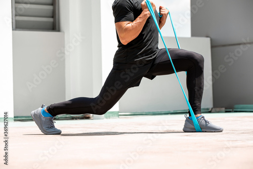 Fotografia, Obraz Athletic man doing lunge workout exercise with resitance band outdoors on buildi