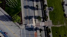 Super Smooth Slow Aerial Dolly Roll Birds Eye View Over English Bay Park Roads, Bike Lanes, Bike Rental Booth Palm Trees Canadian BC LGBTQ Pride Flags Sunny Shadow Crosswalk Cones Pilans COVID-19