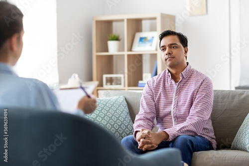 psychology, mental therapy and people concept - young indian man patient and woman psychologist at psychotherapy session