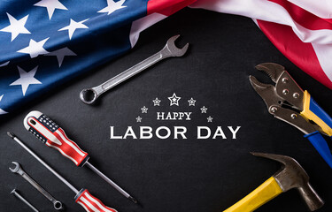 Happy Labor day concept. American flag with different construction tools on black table background, with copy space for text.