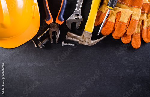 Happy Labor day concept. American flag with different construction tools on black table background.