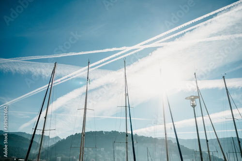 Low angle shot of boat masts under the sky with jet trials Fototapet