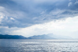 Dark clouds in the open sea. On the horizon are mountains on an island. Blue gradient. - 369698401